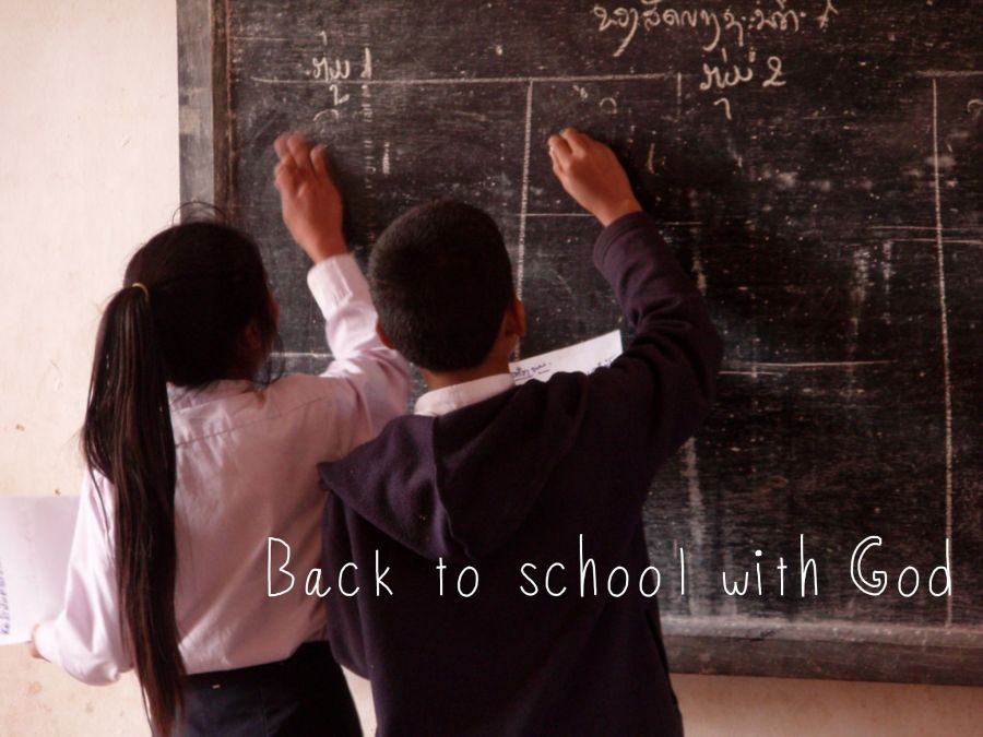 "Image of children writing on blackboard with ""Back to school with God"" in the foreground"