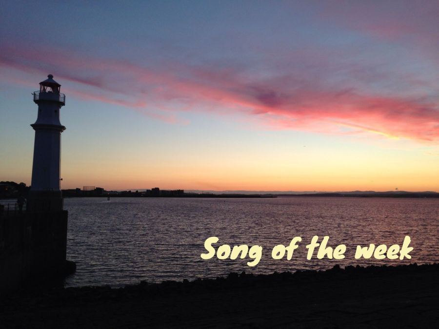 "Photo of Newhaven lighthouse at sunset with pink clouds in the sky, and caption ""Song of the week"""