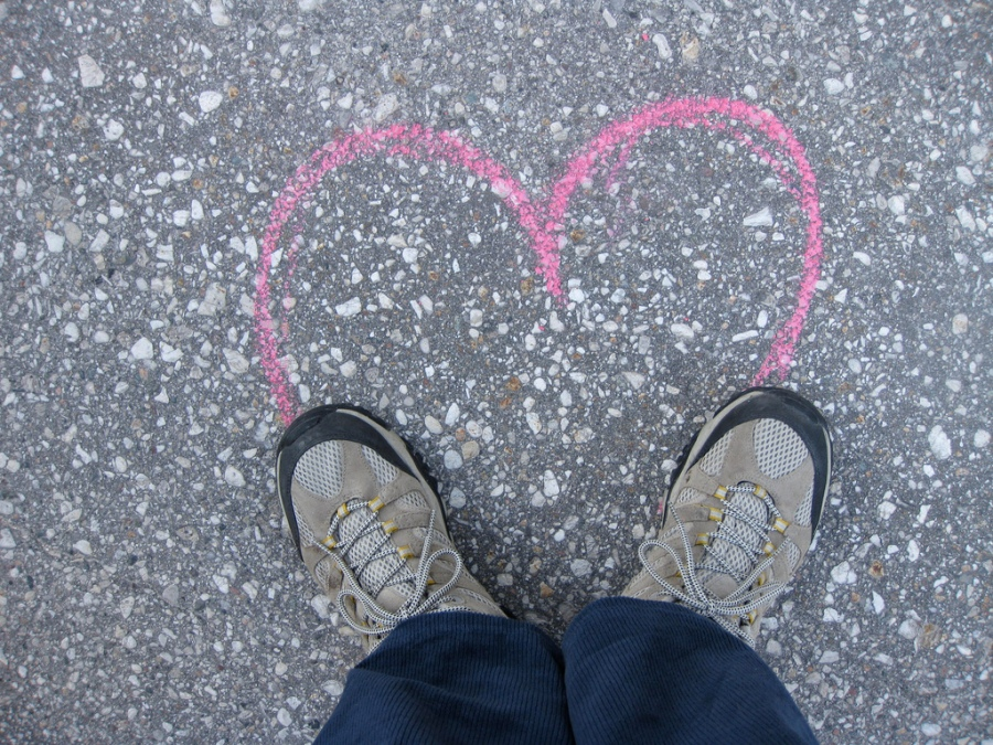 Photo of a heart outlined on the pavement in chalk, completed by feet at the bottom of the heart