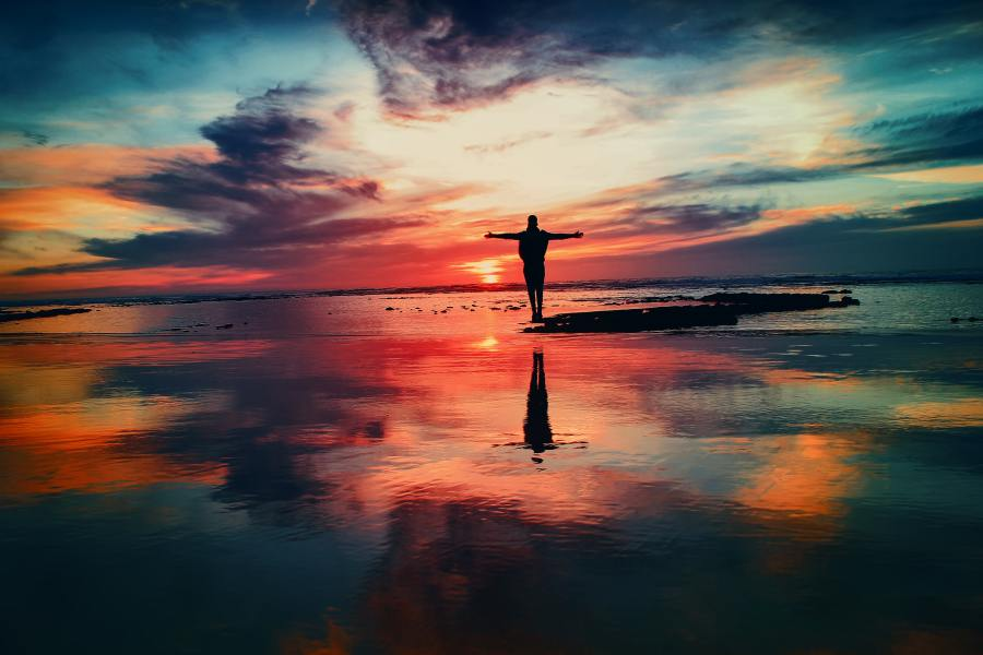 Man standing on a beach with the sunset in the background